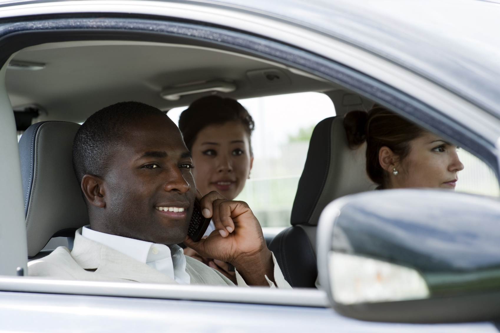 Multi-ethnic businesspeople sharing a car